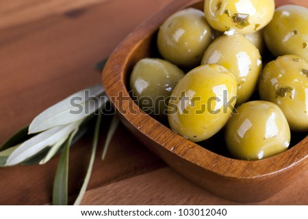 Green olives in a wooden bowl with olive branch, on wooden background.