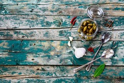 Green olives in glass jar with herbs and spices on rustic wooden texture. Background with space for text.