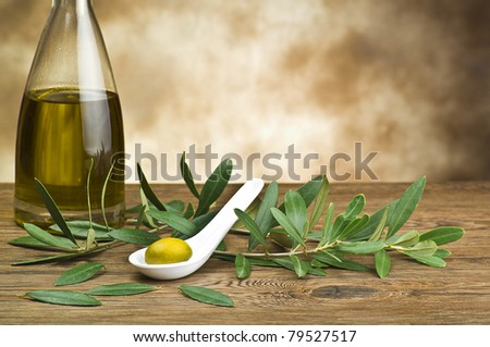 green olives in spoon whit bottle and leaf