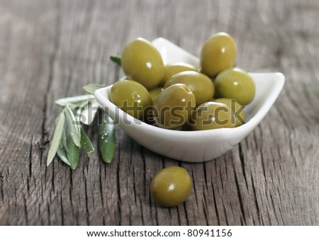 Green olives in the bowl and olive branch on wooden table