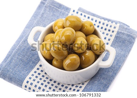 green olives in white porcelain bowl on serviette flat