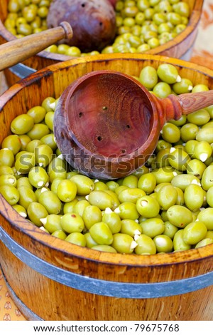 Green olives in wooden bucket sold on market
