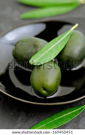 Green olives on black small plate