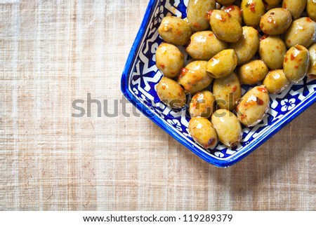 Green olives with red chilli flakes on a blue dish