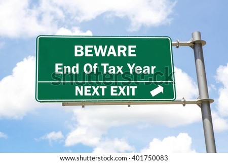 Green overhead road sign with a Beware of the End Of The Tax Year Next Exit concept against a partly cloudy sky background.