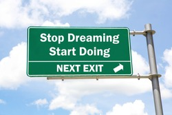 Green overhead road sign with A Stop Dreaming Start Doing Next Exit concept against a partly cloudy sky background.