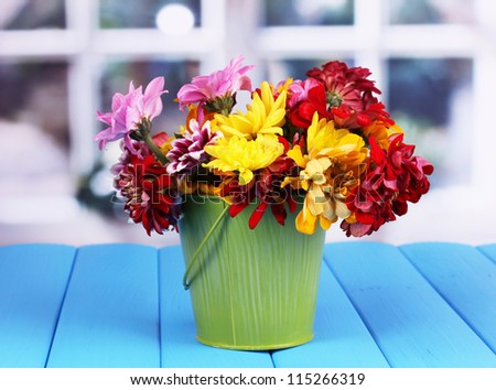 Green pail with flowers on blue wooden table on window background