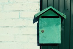 Green painted metal mailbox mounted on a wall