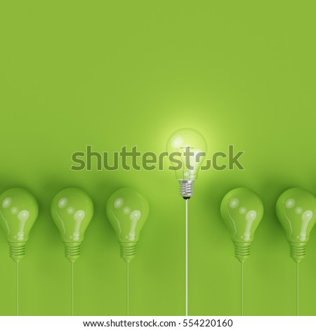 Green pantone light bulbs with glowing one different idea on pastel green background. minimal concept. top view.