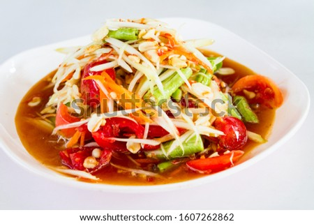 """Green papaya salad Thai cuisine spicy delicious. Thai call """"SOM TAM"""". Famous Thai food, papaya salad, Somtum, Papaya Pok Pok. Closeup Thai Green Papaya Salad with peanuts in white plate on white table"""