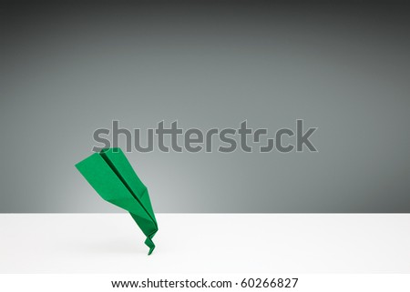 Green Paper airplane with a bent nose