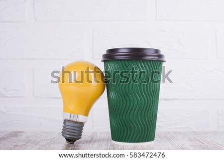 Green paper cup of coffee or tea and a light bulb #583472476