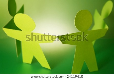green paper cutouts holding hands
