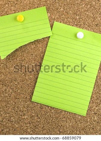 Green paper on cork board with thumb tacks