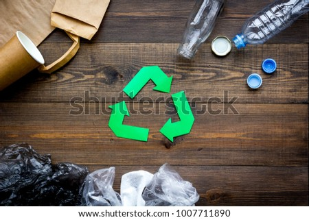 Green paper recycling sign among waste materials paper, plastic, polyethylene on dark wooden background top view copy space