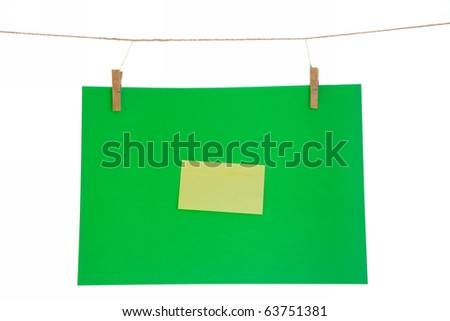 green paper sheet and yellow on a clothes line. Isolated on white background.
