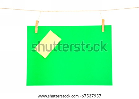green paper sheet and yellow on a clothes line. Isolated on white background. - stock photo
