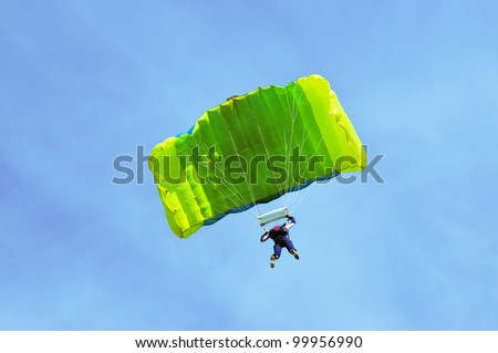 Green parachute on blue sky.
