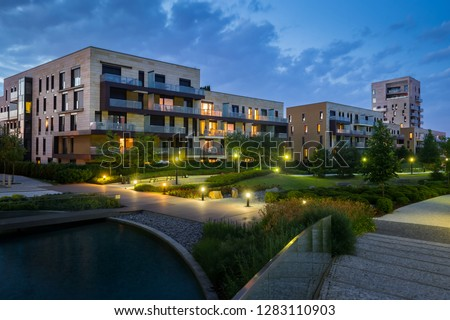 Green park with modern houses in the background in the evening. Illuminated green area with grass and trees. Foto stock ©