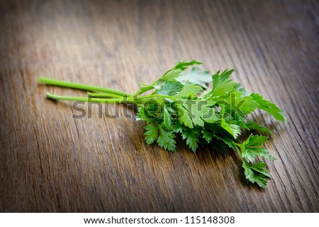 Green parsley lying on a dark brown table.