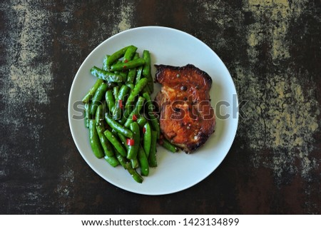 Green pea pods and pork steak on a plate. Balanced nutrition concept. Keto diet. Paleo diet. Pegan Diet.
