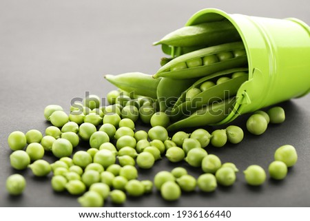 Green pea pods with bucket on black background Stockfoto ©
