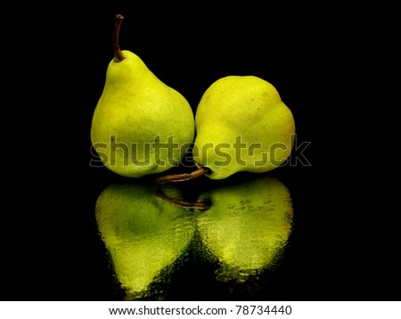 green pear on a black background with water drops