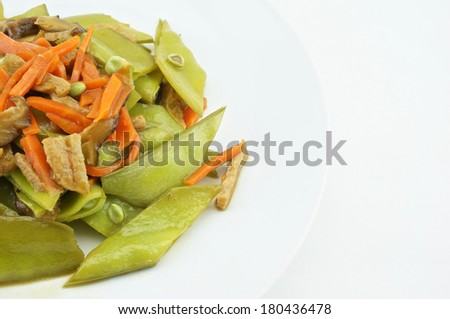 Green peas fried with carrot, mushroom and vegan protein on white dish with white background.