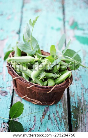 Green peas in a basket made of birch bark
