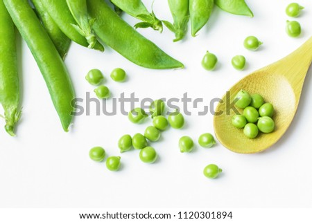 green peas in a wooden spoon close-up. pods of green peas on a white background. background with green peas.