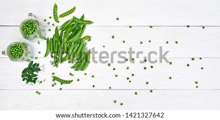 Green peas in jar, pods and pea leaves on white wood table background, copy space. Bio healthy food. Top view, flat lay, above