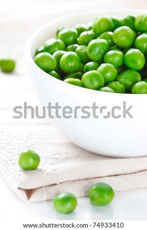 Green peas on a white ceramic bowl close-up.