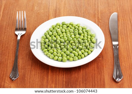 Green peas on plate on wooden background