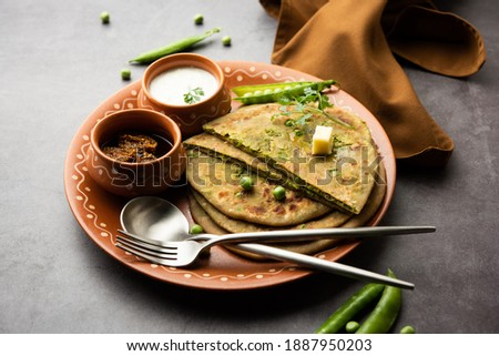 Green Peas or matar ka parathais a Punjabi dish which is an Indian unleavened flatbread made with whole wheat flour,greenpeas. Served with ketchup and curd Foto stock ©