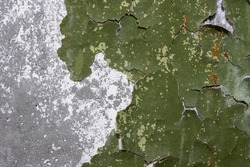 Green peeling paint on the wall. Old concrete wall with cracked flaking paint. Weathered rough painted surface with patterns of cracks and peeling. High resolution texture for background and design.