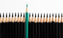 Green pencil standing out from the crowd on white background.