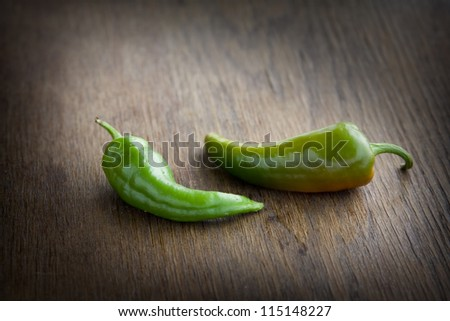 Green pepper lying on a dark brown table.
