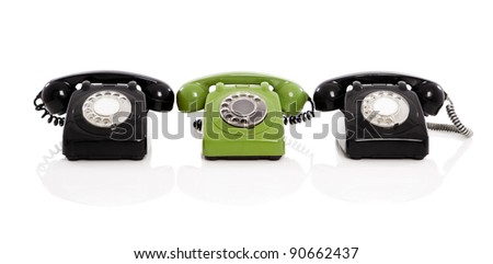 Green phone in the midle of two black phones, isolated on white background - stock photo