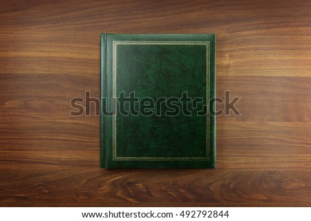 Green Photo album or Year book cover, blank, placed on a dark colored wooden table. Сток-фото ©