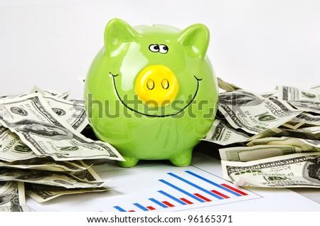 Photo of green piggy bank, bar chart and dollars
