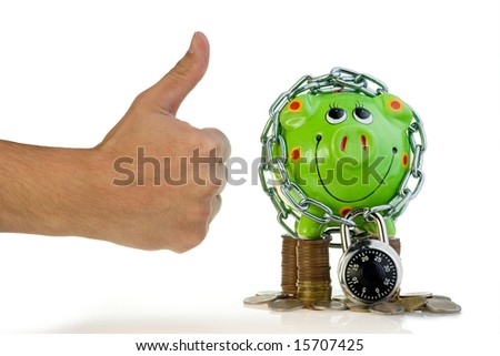 Green piggy bank with chain and padlock on top of stacked coins next to a hand with the 'thumbs up' sign, isolated on white background.