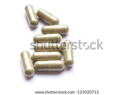 Green pill capsules on white background