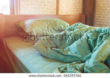 green pillow and blanket with wrinkle messy on bed in vintage wooden bedroom with lighting upper left side, from sleeping in a long night winter.