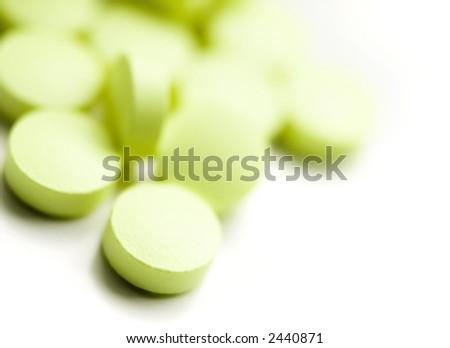 Green pills over white macro shot