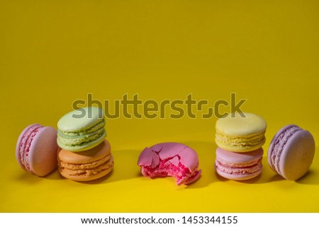 Green pink orange yellow macaroni laid out horizontally, Festive confectionery, sweet cookies, confectionery