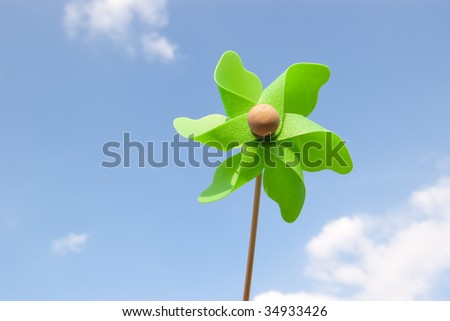 green pinwheel on sky with few clouds - stock photo