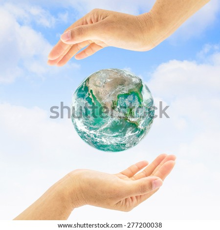 Green planet  between two people hands : Saving environment concept for world health : Green earth among two human hands : World environment day concept :  Elements of this image furnished by NASA.