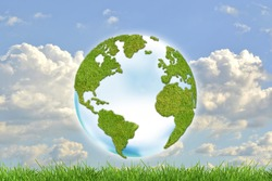 Green planet Earth with grass on blue sky background