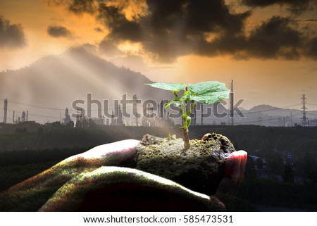 Green plant in hand and industry background , Ecology concept .  #585473531