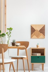 Green plants in small vases on long wooden dining table in bright interior